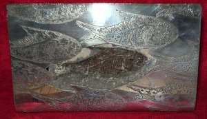Silver ornament based on a fossil fish withe etched shoal